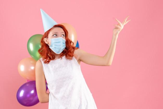 Vista frontale giovane femmina che tiene palloncini colorati in maschera sterile sul rosa
