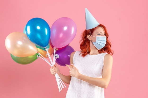 Front view young female holding colorful balloons in sterile mask on pink