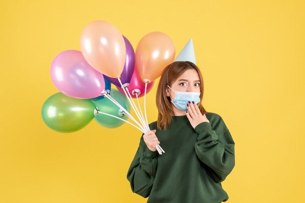 Front view young female holding colorful balloons