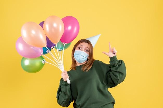 Вид спереди молодая женщина держит разноцветные воздушные шары