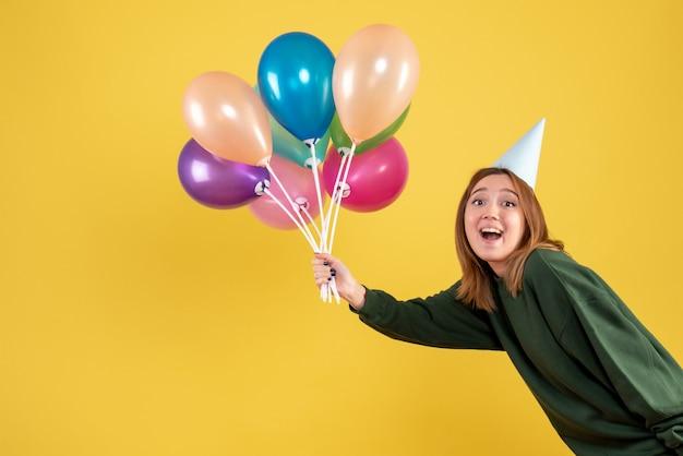 カラフルな風船を保持している正面図若い女性
