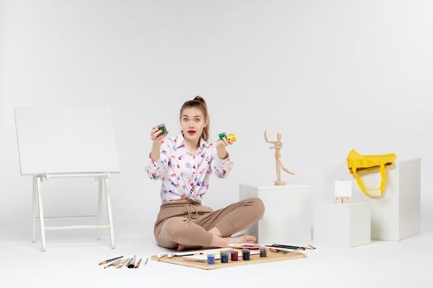 正面図白い背景の上の缶の中にカラフルな塗料を保持している若い女性