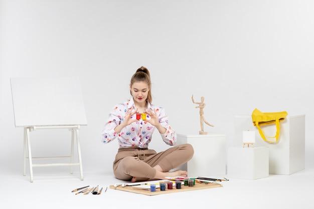 白い背景の上の小さな缶の中にカラフルな塗料を保持している正面図若い女性