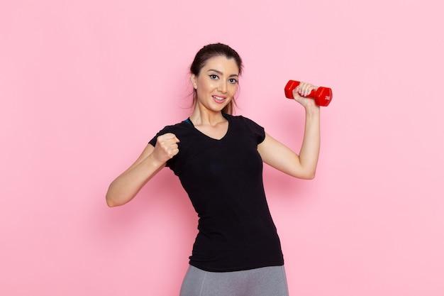正面図ダンベルを保持し、淡いピンクの壁のアスリートスポーツ運動健康トレーニングに笑みを浮かべて若い女性