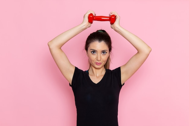Front view young female holding dumbbells on the light-pink desk athlete sport exercise health workout