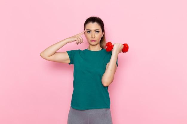 Vista frontale giovane donna in possesso di manubri sulla parete rosa chiaro atleta sport esercizio fisico allenamenti