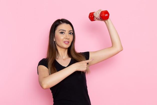 Вид спереди молодая женщина, держащая гантели на светло-розовой стене, спортсмен, спортивные упражнения, оздоровительная тренировка