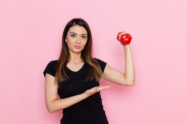 ライトピンクの壁のアスリートスポーツ運動健康トレーニングでダンベルを保持している正面図若い女性