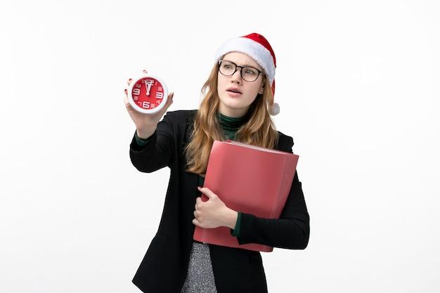 ファイルと白い壁の本の新年のクリスマスの時計を保持している若い女性の正面図