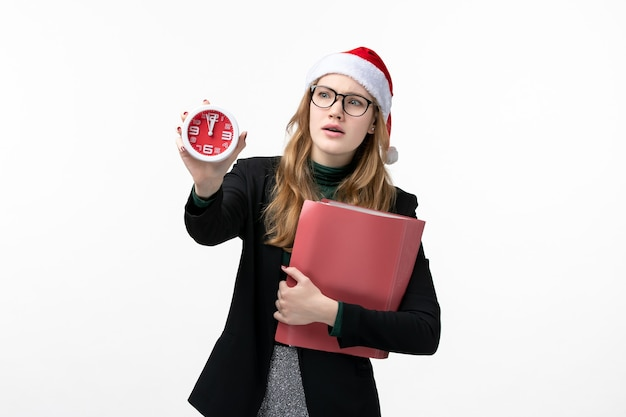 Front view young female holding files and clock on a white wall book new year christmas