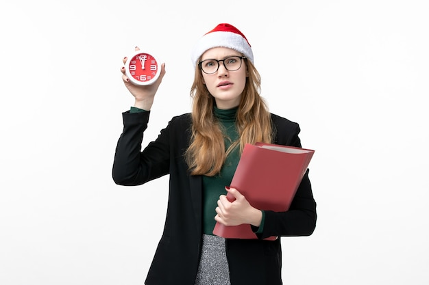Front view young female holding files and clock on white wall books new year christmas