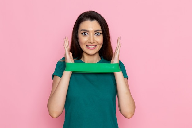녹색 붕대를 들고 밝은 분홍색 벽 운동 스포츠 운동 선수의 아름다움에 웃는 전면보기 젊은 여성