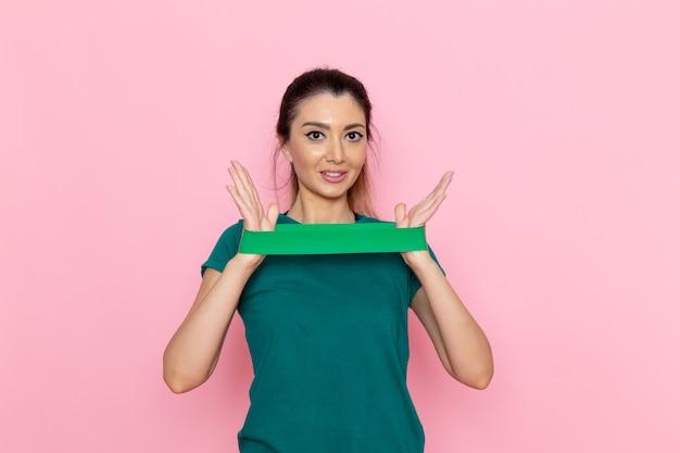 ピンクの壁に緑の包帯を保持している正面図若い女性美容スポーツ運動アスリートトレーニングスリム