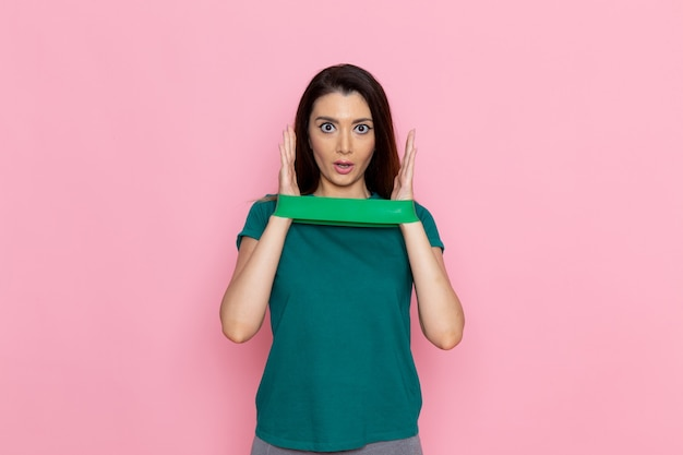 분홍색 벽 운동 스포츠 운동 선수 허리 아름다움에 녹색 붕대를 들고 전면보기 젊은 여성