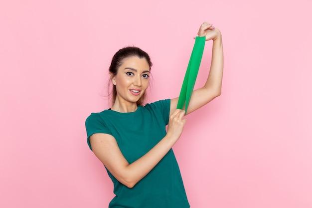 분홍색 벽 아름다움 스포츠 운동 선수 운동 슬림에 녹색 붕대를 들고 전면보기 젊은 여성