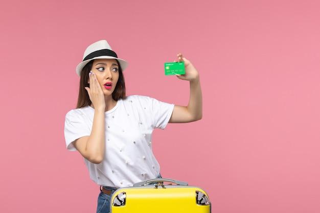 Вид спереди молодая женщина держит зеленую банковскую карту на розовой стене эмоция женщина поездка лето