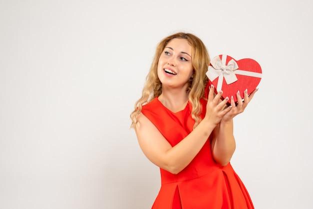 Вид спереди молодая женщина держит подарок в форме сердца