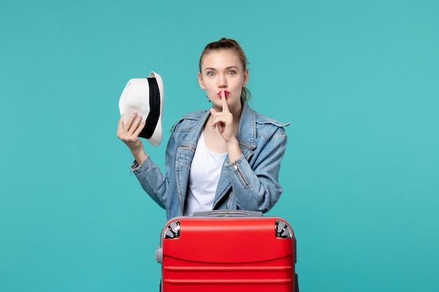 青いスペースで旅行の準備をしている彼女の帽子を保持している正面図若い女性