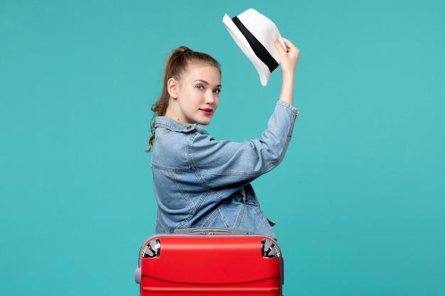 Вид спереди молодая женщина, держащая шляпу, готовится к поездке в синее пространство