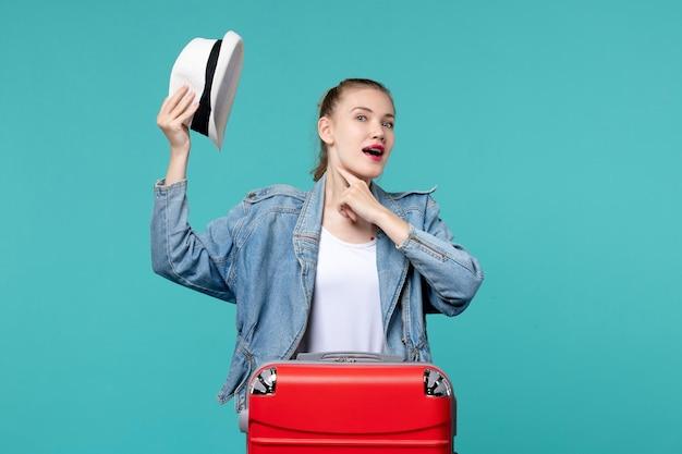 Giovane femmina di vista frontale che tiene il suo cappello e si prepara per il viaggio sullo scrittorio blu