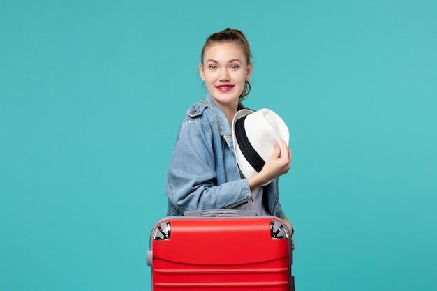 Giovane femmina di vista frontale che tiene il suo cappello che si prepara per il viaggio che sorride sullo spazio blu