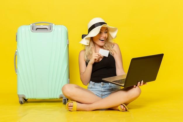 彼女のラップトップと白いカードを保持している正面図若い女性