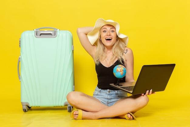 Giovane femmina di vista frontale che tiene il suo computer portatile e globo
