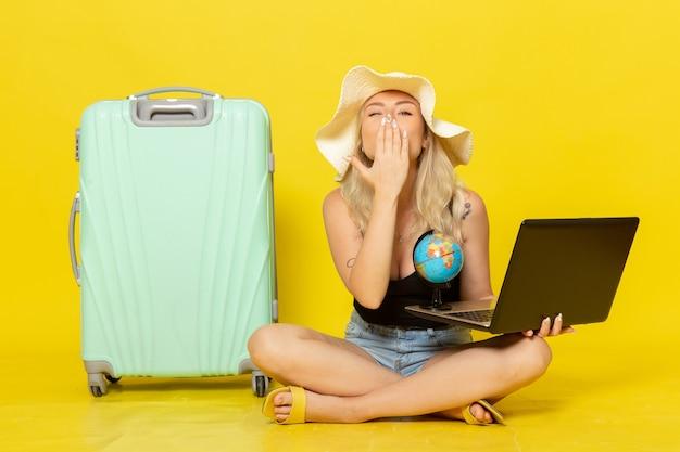 Giovane femmina di vista frontale che tiene il suo computer portatile e che invia i baci dell'aria