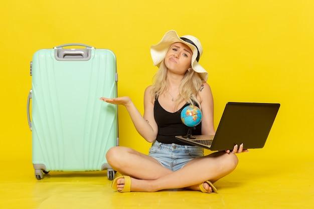 Giovane femmina di vista frontale che tiene il suo computer portatile