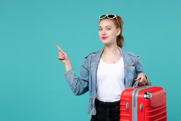 Вид спереди молодая женщина держит свою красную сумку и готовится к поездке в синее пространство