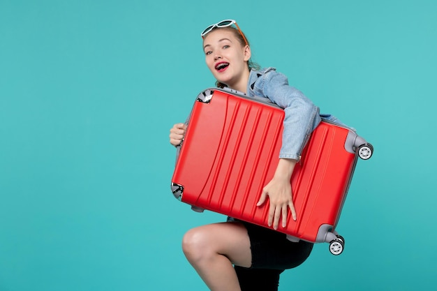 彼女の赤いバッグを保持し、青いスペースでの旅行の準備をしている正面図若い女性