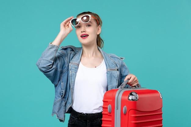 Вид спереди молодая женщина держит свою красную сумку и готовится к поездке на голубом пространстве
