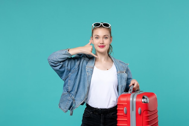 그녀의 빨간 가방을 들고 푸른 공간에 미소 여행을 준비하는 전면보기 젊은 여성