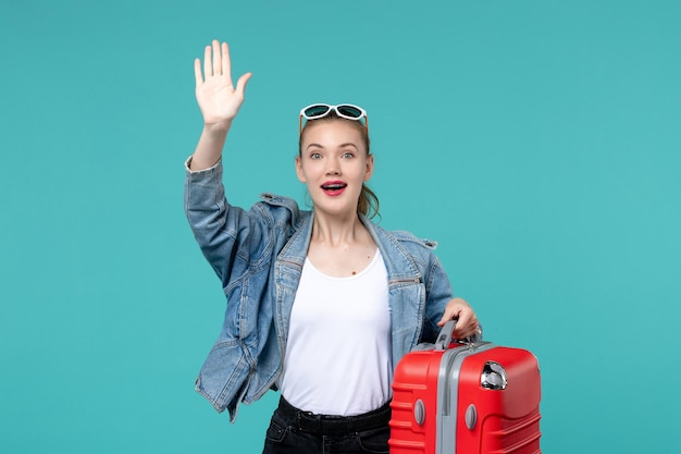 Вид спереди молодая женщина, держащая свою красную сумку и готовящаяся к поездке, машет рукой на синем пространстве