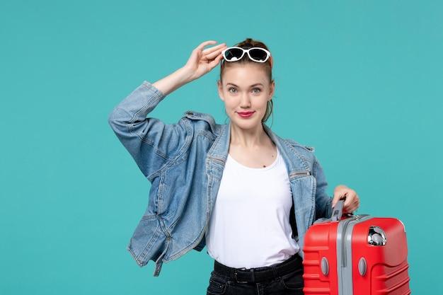 Giovane femmina di vista frontale che tiene la sua borsa rossa e che prepara per il viaggio sul viaggio di viaggio di vacanza di viaggio del des blu