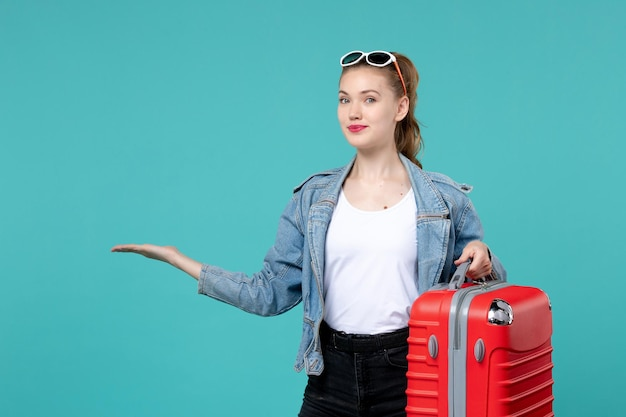 Front view young female holding her red bag and preparing for trip on blue space