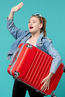Front view young female holding her red bag and preparing for trip on light-blue space