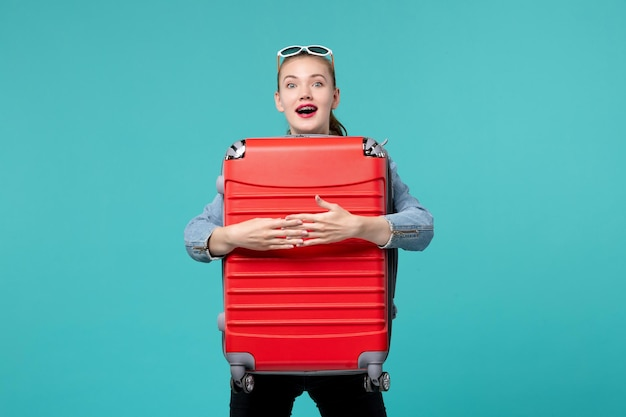 Front view young female holding her red bag and preparing for vacation on blue space