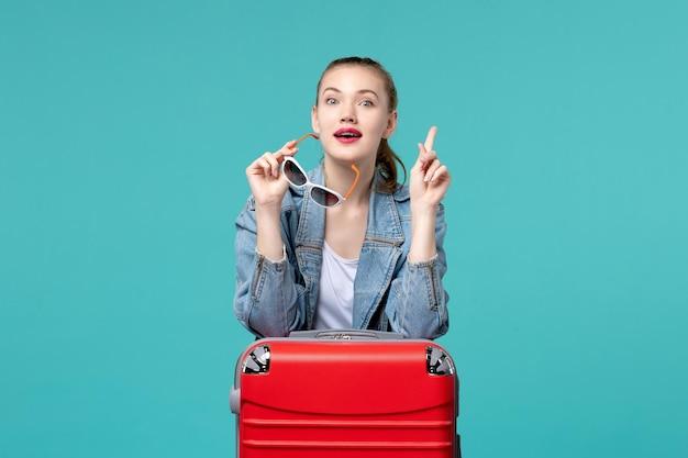Вид спереди молодая женщина держит свои солнцезащитные очки, готовясь к отпуску на синем столе
