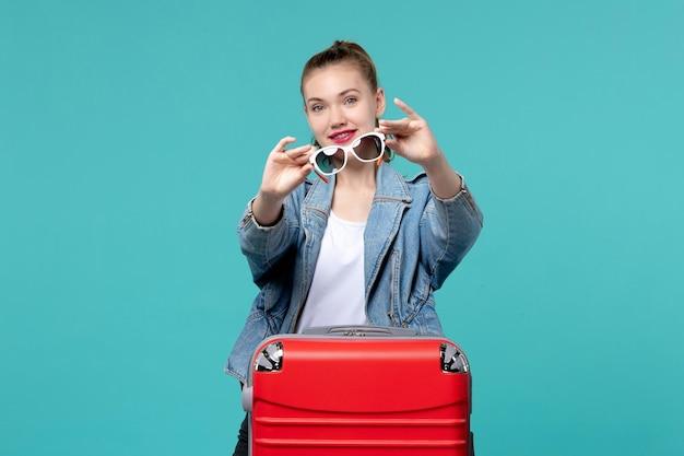 Giovane femmina di vista frontale che tiene i suoi occhiali da sole che si preparano per la vacanza sullo spazio blu