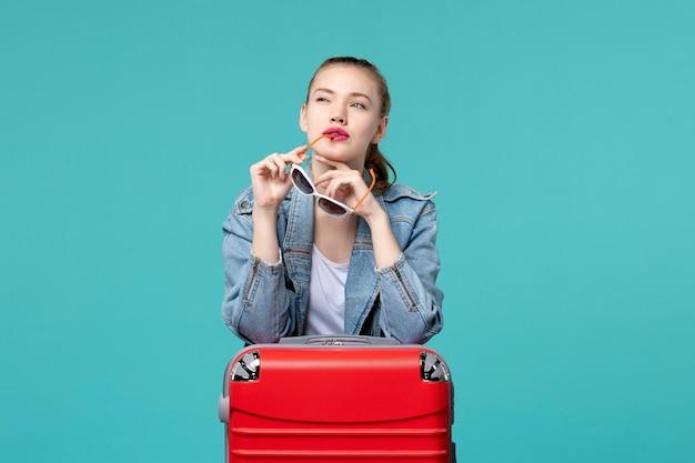 Giovane femmina di vista frontale che tiene i suoi occhiali da sole che si preparano per le vacanze sullo spazio azzurro