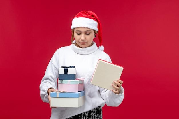 正面図赤い背景に休日のプレゼントを保持している若い女性