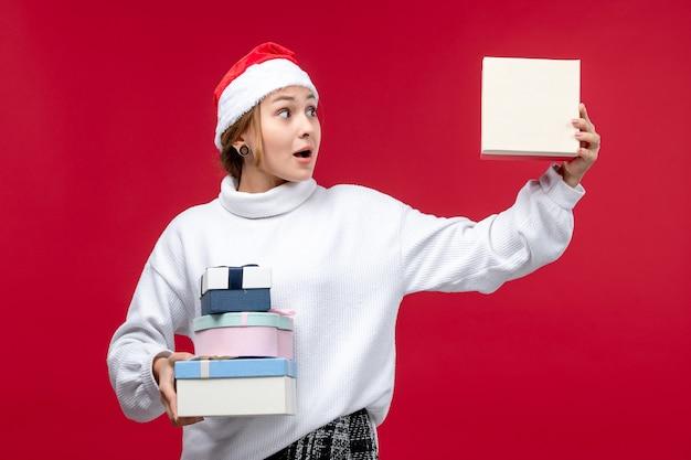 휴일을 들고 전면보기 젊은 여성 빨간색 배경에 선물