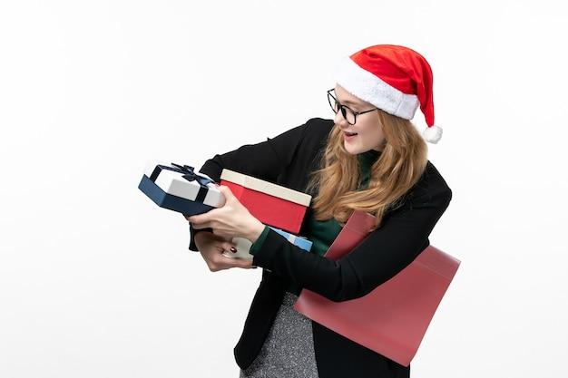 Вид спереди молодая женщина держит праздничные подарки на белой стене, подарок рождество, новый год