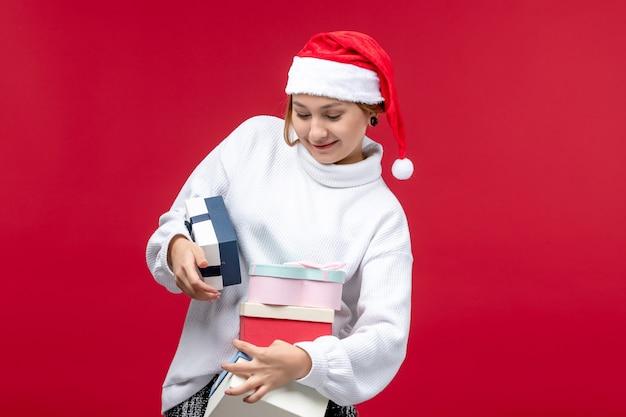 Вид спереди молодая женщина держит праздничные подарки на красном фоне