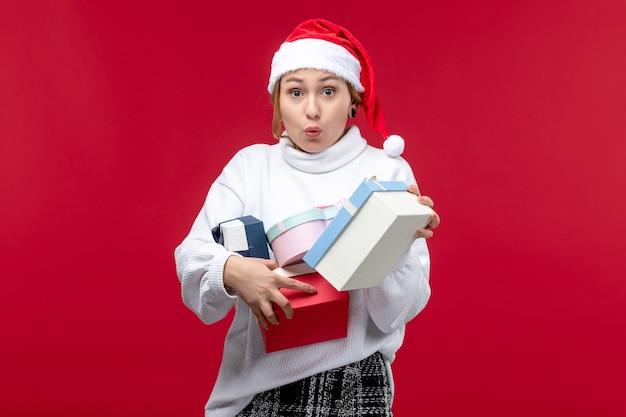 赤い机の上で休日のプレゼントを保持している正面図若い女性