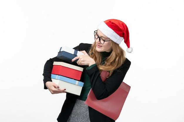 Вид спереди молодая женщина держит праздничные подарки на белом столе, подарок на рождество, новый год
