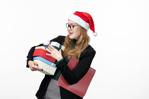 Front view young female holding holiday presents on a white wall gift book new year