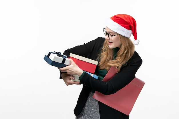 Front view young female holding holiday presents on a white wall gift christmas new year