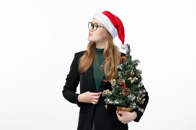 흰 벽 장난감 새 해 크리스마스에 크리스마스 트리를 들고 전면보기 젊은 여성